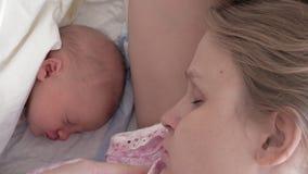 Vermoeide en slaperige moeder die op pasgeboren baby letten stock footage