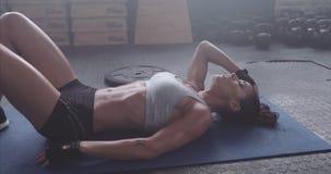 Vermoeide en uitgeputte vrouwelijke atleet die op gymnastiekvloer liggen stock footage