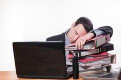 Vermoeide en uitgeputte werknemersslaap op het werk stock fotografie
