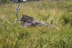 Vermoeide fiets die in het gras bij de kant van de weg liggen Royalty-vrije Stock Afbeeldingen