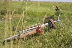 Vermoeide fiets die in het gras bij de kant van de weg liggen Stock Fotografie