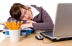 Vermoeide geïsoleerdez beambteslaap op haar bureau, Stock Foto