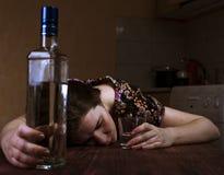 Vermoeide gedronken vrouwenslaap op de lijst stock fotografie