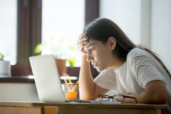 Vermoeide gefrustreerde vrouw die aandachtig een contract op laptop lezen stock fotografie