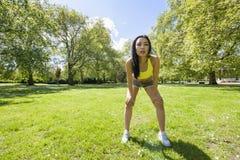 Vermoeide geschikte vrouw die een onderbreking nemen terwijl het uitoefenen in park Stock Foto's