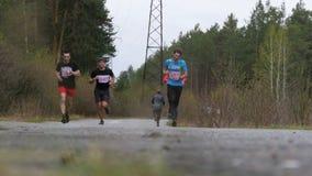 Vermoeide groep jonge atleten die langs een weg in bos langzame motie lopen stock video
