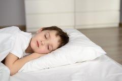 Vermoeide jong geitjeslaap in bed, gelukkige bedtijd in witte slaapkamer Royalty-vrije Stock Foto