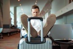 Vermoeide jonge die mens op zetel in luchthavenzaal wordt aangestoken Kerelslaap Hij leunt op koffer stock foto