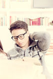 Vermoeide jonge mens die met glazen een boek lezen Royalty-vrije Stock Foto