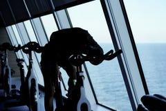 Vermoeide jonge vrouw die bij het spinnen van fiets situeren royalty-vrije stock afbeelding