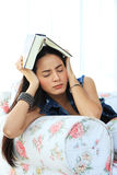 Vermoeide jonge vrouw die een dutje nemen die thuis op bank met een boek liggen Stock Foto's