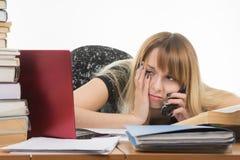 Vermoeide jonge vrouwenbeambte die op telefoon spreken en monitor bekijken stock fotografie