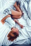 Vermoeide jonge vrouwenslaap op bed royalty-vrije stock foto's