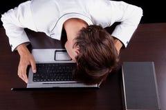 Vermoeide jonge zakenman met hoofd op de computer royalty-vrije stock foto