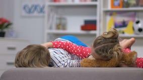 Vermoeide kinderen die op bank na actief spel, zuster strijkende broer ontspannen stock videobeelden