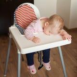 Vermoeide kindslaap in highchair na de lunch Leuke baby die zijn gezicht op het lijstdienblad girllying Stock Fotografie