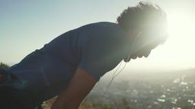 Vermoeide mannelijke atleet die met oortelefoons in zijn oren na het uitoefenen ontspannen stock video
