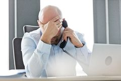 Vermoeide medio volwassen zakenman die landline telefoon met behulp van bij bureau in bureau royalty-vrije stock afbeelding