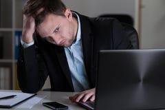 Vermoeide mens in bureau Stock Afbeelding