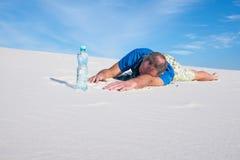 Vermoeide mens die die aan dorst lijden in de woestijn wordt verloren stock fotografie