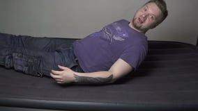 Vermoeide mens die op opblaasbare matras vallen stock videobeelden
