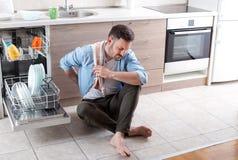 Vermoeide mens naast open afwasmachine Stock Fotografie