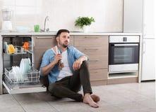 Vermoeide mens naast open afwasmachine Stock Afbeelding