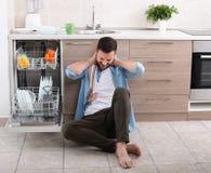Vermoeide mens naast open afwasmachine Stock Foto's