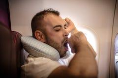 Vermoeide mens in vliegtuig traveling stock foto
