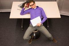 Vermoeide mens in zijn bureau Stock Afbeeldingen