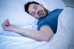 Vermoeide mensenslaap en het snurken luid in het bed royalty-vrije stock fotografie