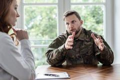 Vermoeide militair die met oorlogssyndroom met therapeut tijdens vergadering in het bureau spreken royalty-vrije stock afbeeldingen