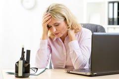 Vermoeide onderneemster op middelbare leeftijd in haar bureau Stock Afbeeldingen