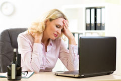 Vermoeide onderneemster op middelbare leeftijd in haar bureau Stock Afbeelding