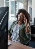Vermoeide overwerkte onderneemster die computer in een bureau bekijken royalty-vrije stock foto