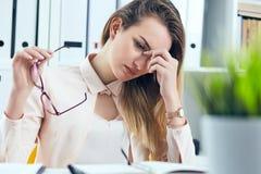 Vermoeide overwerkte onderneemster in glazen op kantoor die haar gezicht behandelen met hand stock foto