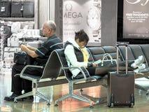 Vermoeide reizigers die bij de luchthaven wachten Stock Afbeelding