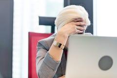 Vermoeide rijpe onderneemster met hoofd in handen op kantoor Stock Afbeelding