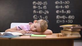 Vermoeide schooljongen die op gevallen bureau dutten, in slaap terwijl het voorbereiden van taak stock footage