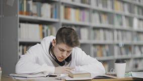Vermoeide in slaap kereldalingen terwijl het bestuderen bij bibliotheek bij universiteit stock video