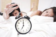 Vermoeide spleepy vrouwen die een bellende klok tegenhouden Royalty-vrije Stock Foto's