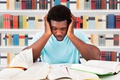 Vermoeide student in bibliotheek royalty-vrije stock foto