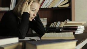 Vermoeide student die in de bibliotheek in universiteit bestuderen Vrouwelijke studentenzitting bij het bureau en de grepen haar  stock videobeelden