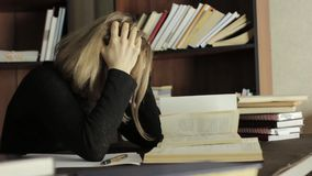 Vermoeide student die in de bibliotheek in universiteit bestuderen Vrouwelijke studentenzitting bij het bureau en de grepen haar  stock footage