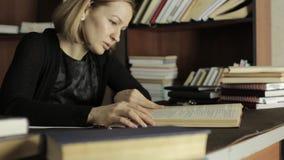 Vermoeide student die voor examens in de bibliotheek in universitaire universiteit voorbereidingen treffen stock footage