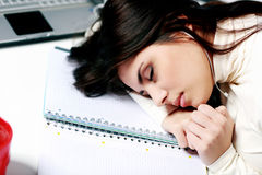 Vermoeide student gevallen in slaap bij de lijst Stock Foto