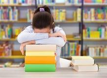 Vermoeide Student Leaning On Books in Bibliotheek royalty-vrije stock foto
