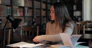 Vermoeide Student Studying in Bibliotheek, Hoofdpijn stock video
