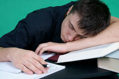 Vermoeide studentenslaap bij het bureau Stock Afbeeldingen
