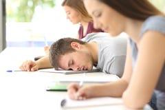 Vermoeide studentenslaap in een klasse bij klaslokaal stock foto